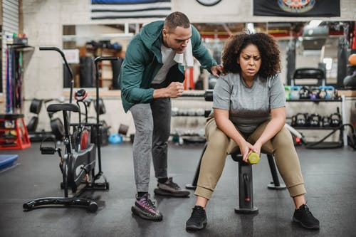 Personal male trainer with overweight female client in fitness center