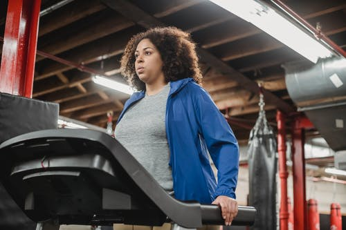 Low angle of plump African American female standing on treadmill in gym and looking away