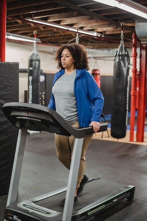 Full body of plump serious female in sportswear exercising on treadmill in modern sport club