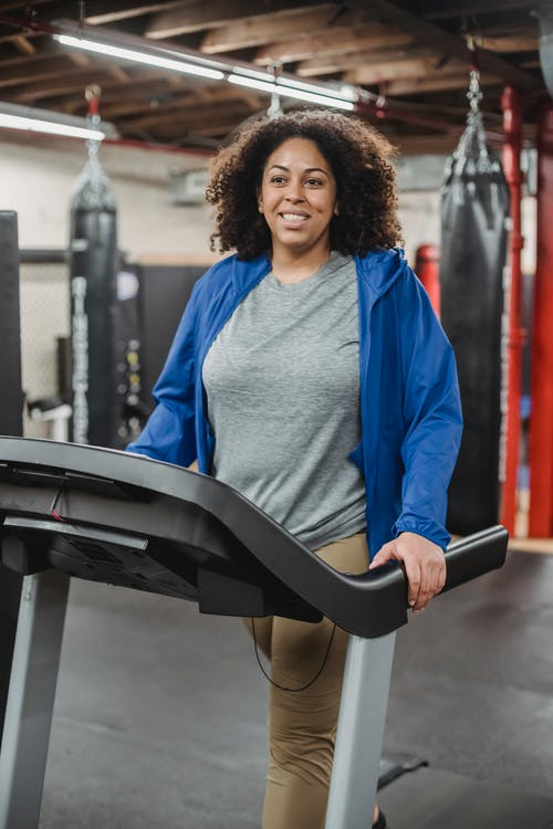 Smiling woman on treadmill in gym