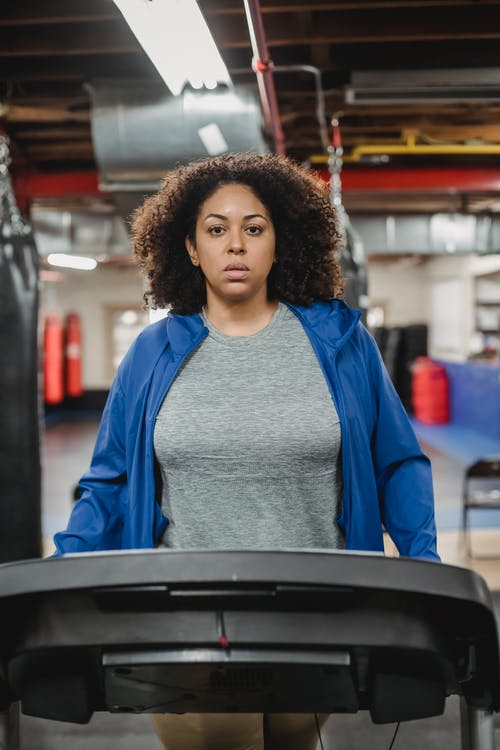 Serious woman walking on treadmill during workout