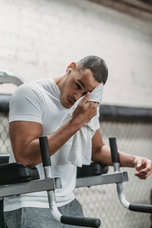 Young male wiping forehead with towel during rest after hard workout in contemporary fitness center
