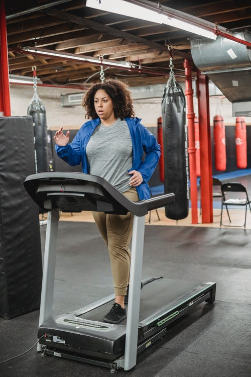 Tired woman running on treadmill in contemporary gym