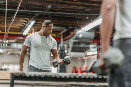 Crop black man doing exercise with dumbbells