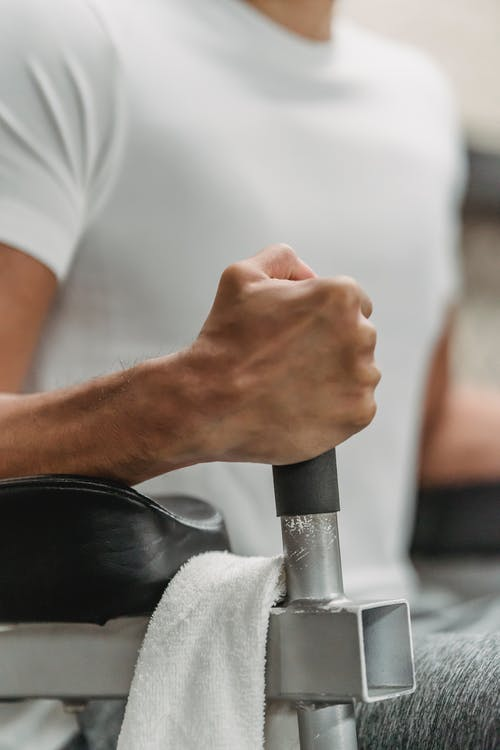 Crop unrecognizable muscular ethnic sportsman in white t shirt training in gym in daylight