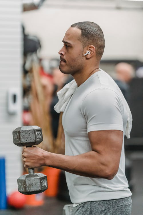 Side view of strong muscular African American sportsman in sportswear training with dumbbells in gym
