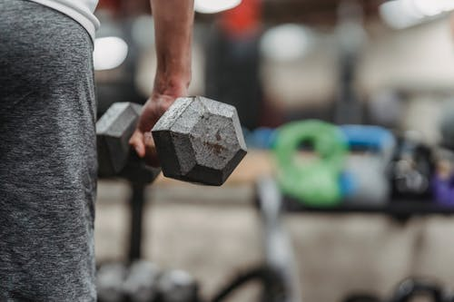 Ethnic sportsman training with dumbbells in gym