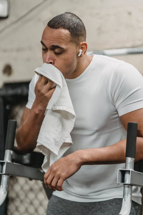 Strong sportsman resting after workout while listening music in earbuds and wiping face with towel in gym