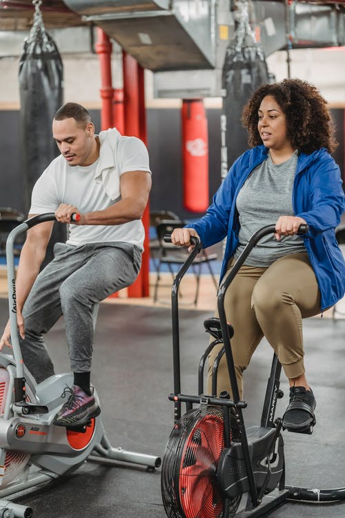 Black man and woman exercising on cycling machine