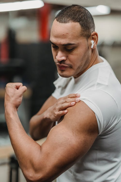 Muscular sportsman doing exercises in gym