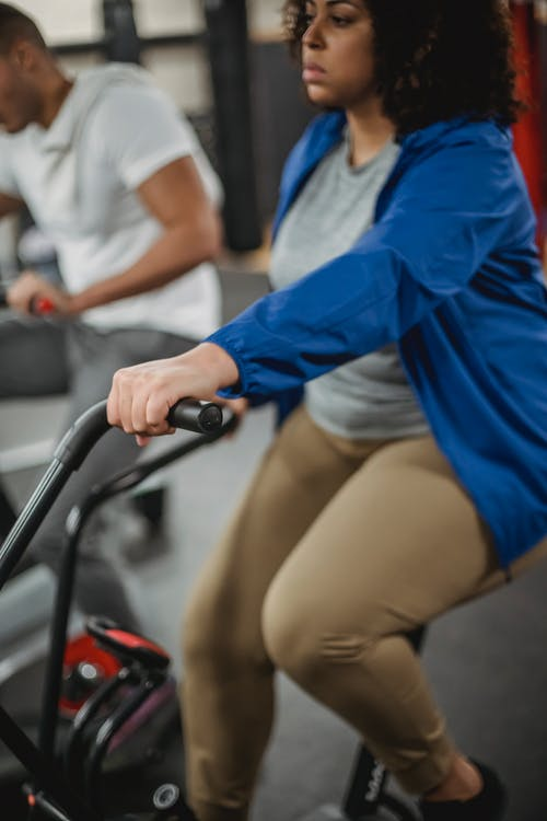 Crop plump black woman riding stationary bike in gym