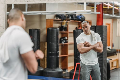 Wistful ethnic sportsman looking at biceps reflecting in gym mirror