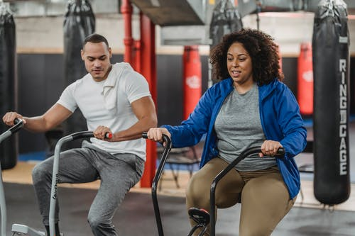 Plus sized African American female in sportswear exercising on stationary bicycle near fit muscular male coach in modern gym