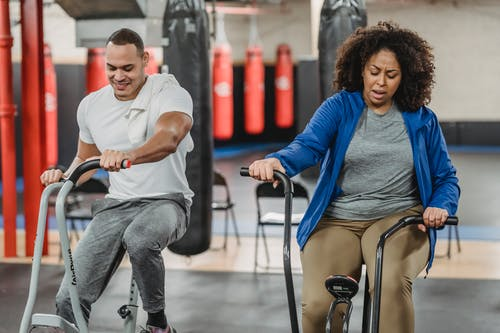 Plump black woman and muscular sportsman cycling in gym