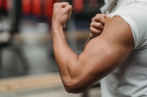 Crop anonymous sportsman in white shirt demonstrating biceps while training in modern gym