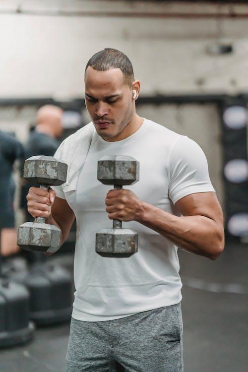Man in White Crew Neck T-shirt Holding Two Dumbbells
