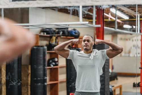 Strong ethnic sportsman showing biceps and reflecting in gym mirror