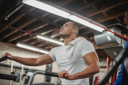 Strong ethnic sportsman exercising on stationary bike in gym