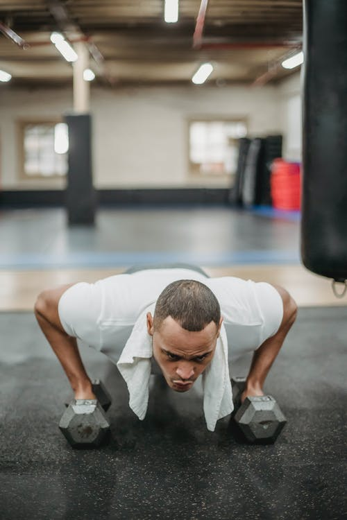 Strong ethnic sportsman in activewear doing pushups with dumbbells in modern equipped fitness club