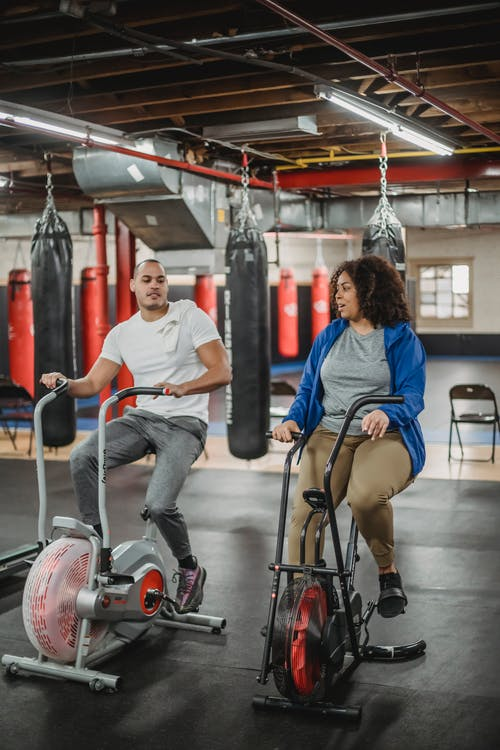 Diverse trainee and coach exercising on bicycles in gym