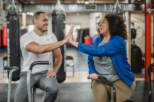 Happy plump African American female trainee and muscular smiling coach clapping each others hands while sitting on stationary bicycles in modern gym