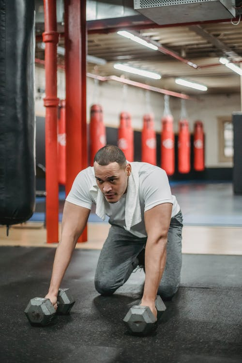 Strong ethnic sportsman exercising with dumbbells on gym floor