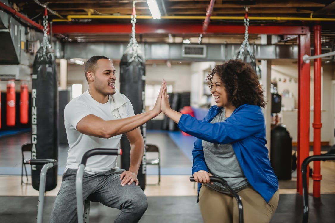 Cheerful plump African American female trainee and fit smiling male coach clapping each others hands while training in spacious equipped gym