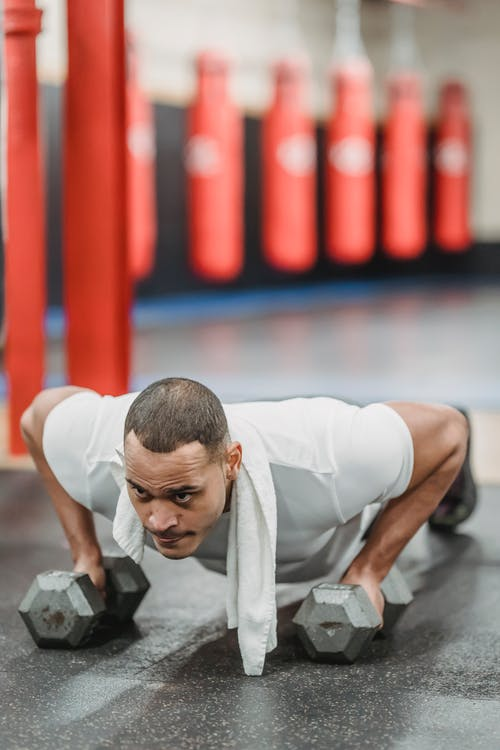Concentrated muscular sportsman performing push ups on dumbbells in modern gym and looking away