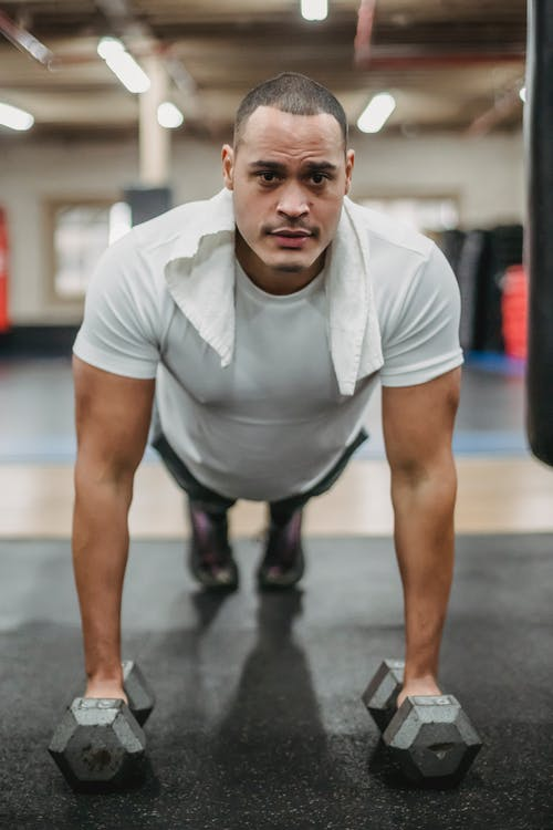 Strong sportsman performing push ups on dumbbells