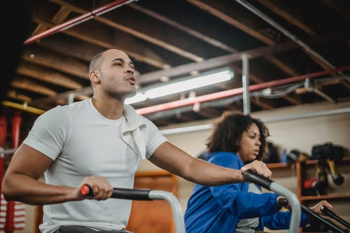 Determined diverse sportspeople exercising on stationary bikes in gym