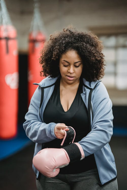 Plump black woman putting on boxing gloves in gym