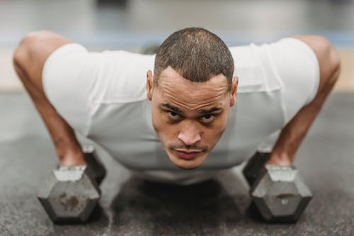 Focused ethnic man doing push up with dumbbells
