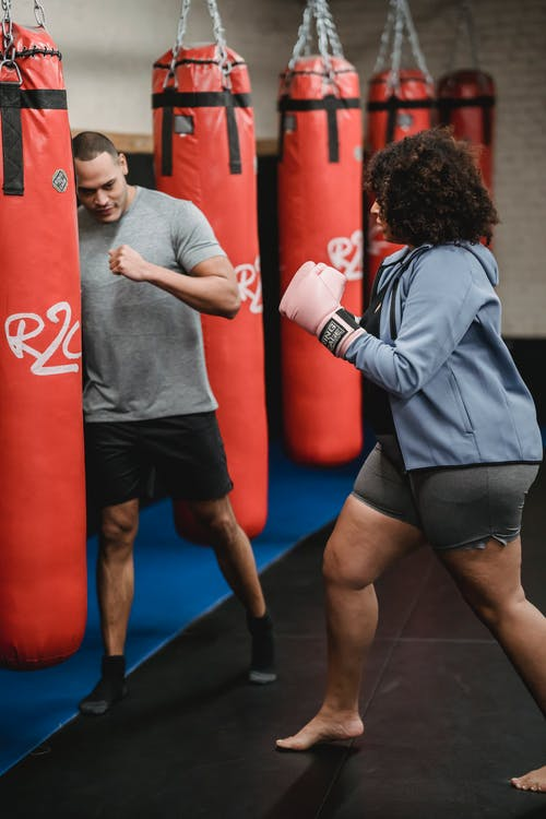 Serious African American barefoot female hitting heavy punching bag while practicing boxing with ethnic personal instructor