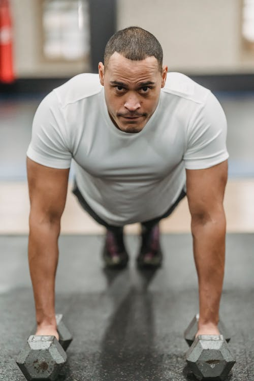 Full body of focused ethnic male standing in plank position with dumbbells while exercising in gym