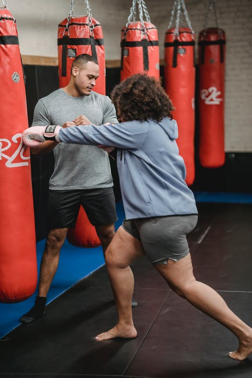 Full body of plus size African American female in boxing gloves hitting punching bag during weight loss training with coach