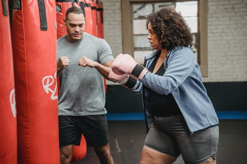 Ethnic trainer showing hit bag to plus size blag female