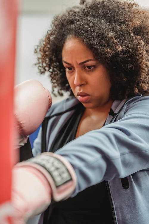 Determined black woman in gloves at boxing training