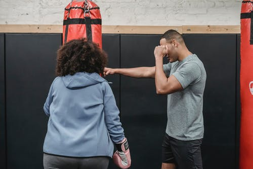 Ethnic trainer showing exercise to female in boxing club