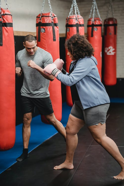 Strong ethnic man showing stance to overweight African American woman in boxing gloves hitting punching bag