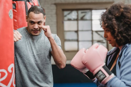 Concentrated ethnic male trainer with fists training with African American wearing boxing gloves in gym