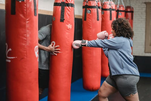 Black woman hitting punching bag during workout with trainer