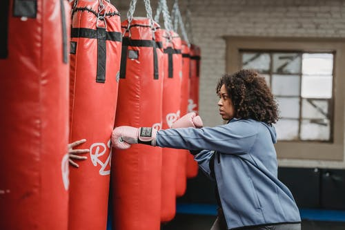 Focused black woman hitting punching bag held by trainer