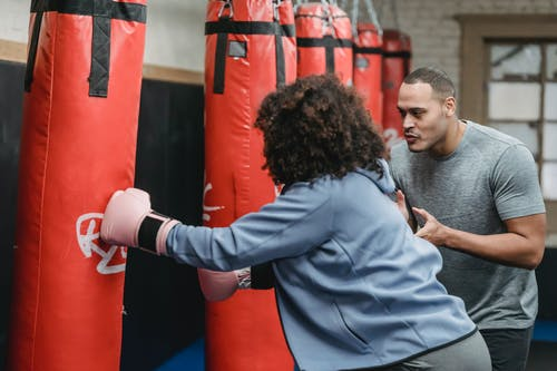 Ethnic male trainer cheering black woman hitting punching bag