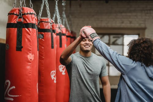 Positive ethnic male coach having high five with female after boxing training in gym with punching bags