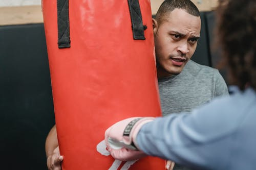 Ethnic male trainer supporting woman during boxing training