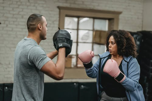 Serious black woman having boxing training with ethnic personal instructor