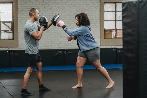 Side view of concentrated overweight African American female in boxing gloves hitting personal trainer during workout