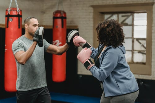 Black instructor helping anonymous woman practicing boxing in gym