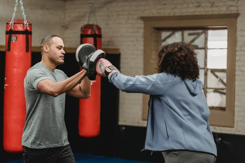 Ethnic trainer working out with unrecognizable boxer in gym