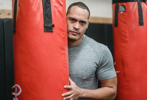 Adult serious ethnic male athlete with muscles in t shirt looking at camera between punching bags in gymnasium